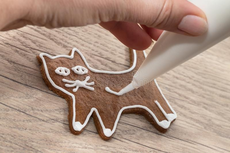 A hand painting sweet cat using a icing bag with sugar frosting stock images