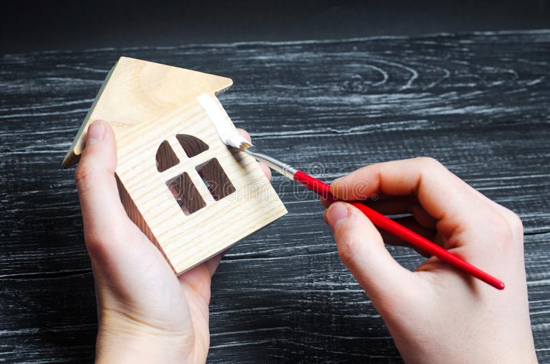 Hand paints a house. Concept of repair, hobby, work. Repair and royalty free stock images