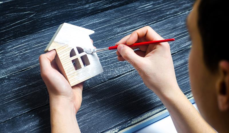 Hand paints a house. Concept of repair, hobby, work. Repair royalty free stock photo