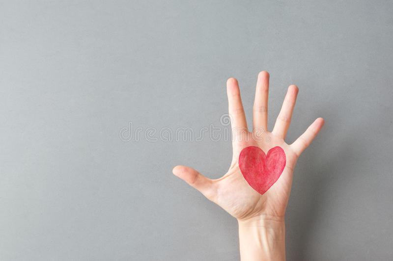 Hand palm of young Caucasian woman girl with painted on red heart on gray wall background. Charity love donation Valentine health royalty free stock photos