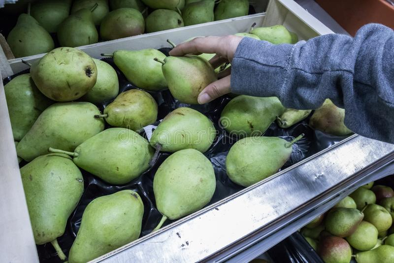 Hand peaking pear in supermarket stock photography