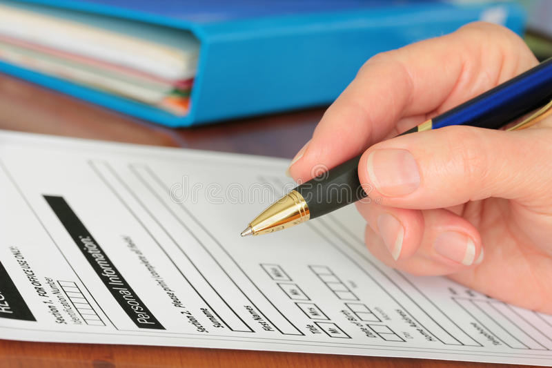 Hand with Pen Completing Personal Info on Form royalty free stock image