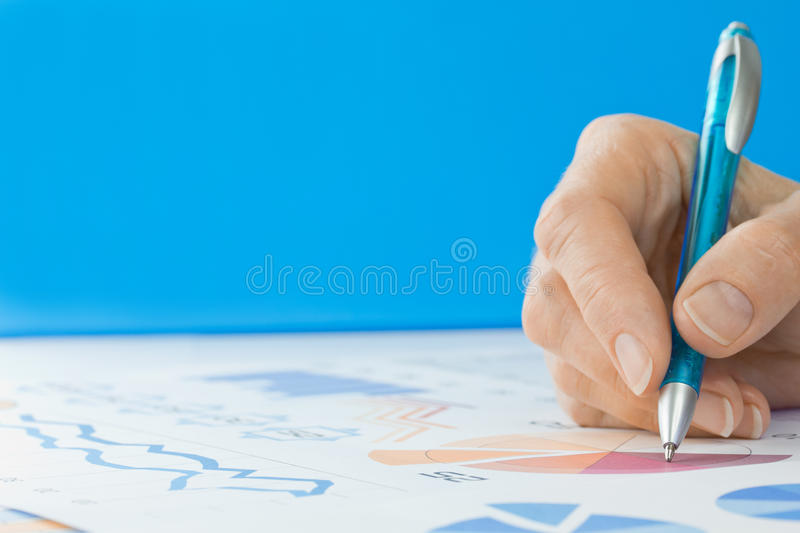 Hand with Pen Editing Graphs. Blue background with copy space royalty free stock images