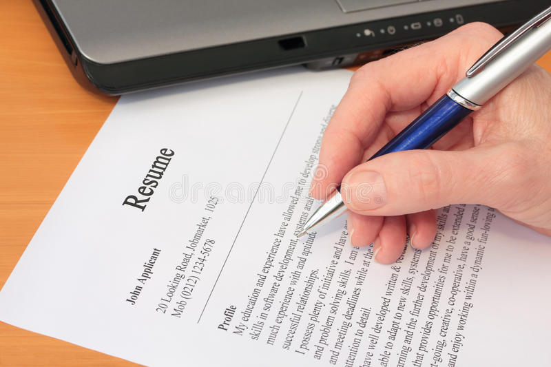 Hand with Pen Proofreading a Resume by Laptop royalty free stock photography