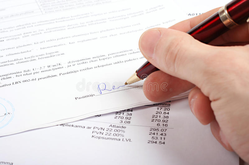 Hand with pen signing contract stock photography