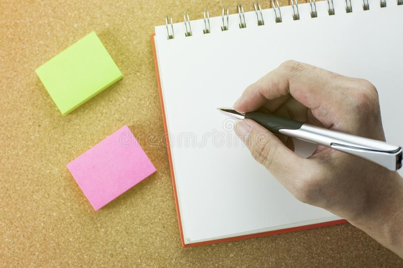 Hand with pen writing on spiral notebook with notepad. royalty free stock images