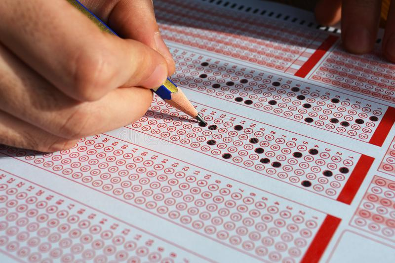 Hand with pencil filling out answers on exam test answer sheet stock images
