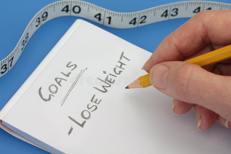 Hand with Pencil making goals list to lose weight stock image