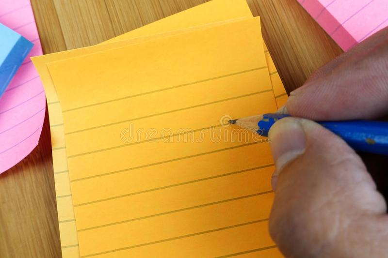 Hand pencil writes in a blank orange notepad royalty free stock image