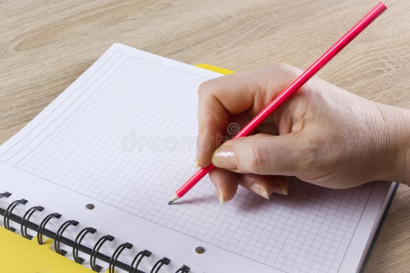 Hand with a pencil. A hand with a pencil writes in a notebook royalty free stock photos