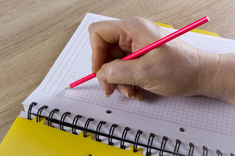 Hand with a pencil. A hand with a pencil writes in a notebook royalty free stock image