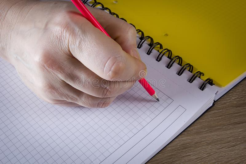 Hand with a pencil. A hand with a pencil writes in a notebook royalty free stock photography