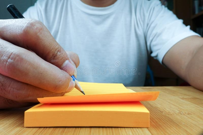 Hand pencil writes in a orange notepad royalty free stock image