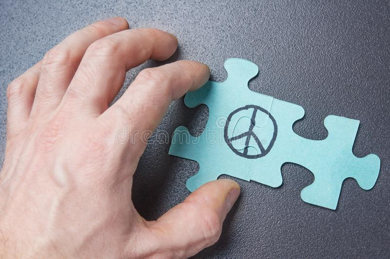Hand of person collects puzzle with symbol of pacifism. Peace sign on puzzle. World Day of Peace concept. royalty free stock photo