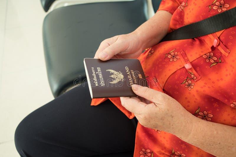 Hand person hold passport thailand in airport for travel. Elder lady hand person hold passport thailand in airport for travel stock photo