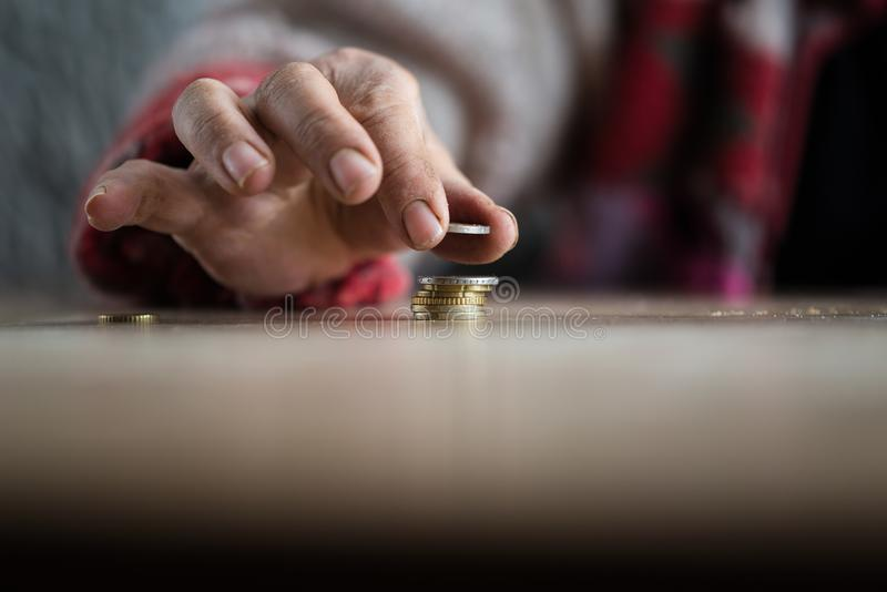 Hand of person putting coin on pile royalty free stock photo