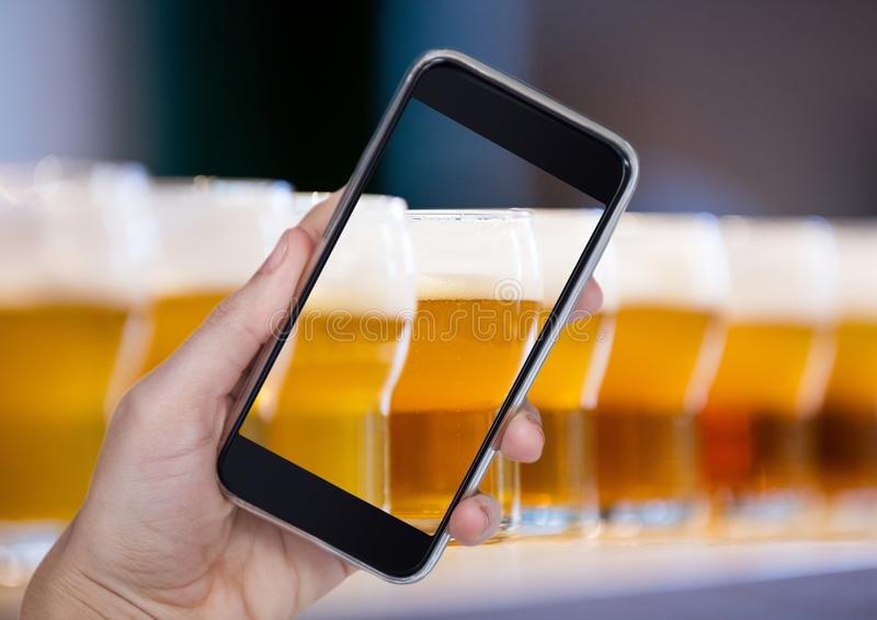 Hand of person taking a picture of beers with her smartphone. Digital composite of Hand of person taking a picture of beers with her smartphone stock images