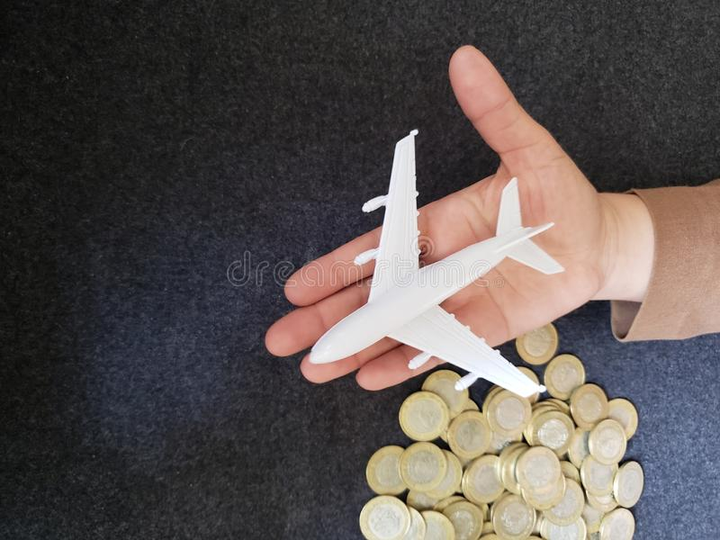 Hand of a person with a white airplane figure and savings in mexican pesos. Trading and exchange, bank and commerce, price of buy and sell, cash value and money stock photo