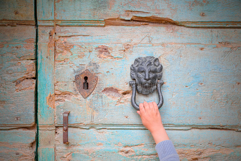 Hand of a person who knocks at a door knocker in the shape of medieval lion hoping to be accepted. Hand of a person who knocks at a door knocker in the shape of royalty free stock photo