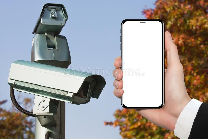 Hand with phone on background of surveillance camera. White screen royalty free stock images