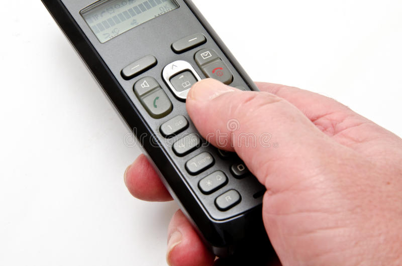 Hand phone. Hand holding a cordless phone in the foreground royalty free stock image