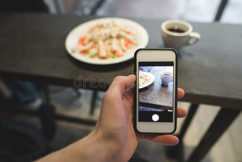 The hand with the phone makes a photo of the food in the restaurant. A salad and coffee photo on a smartphone stock photography