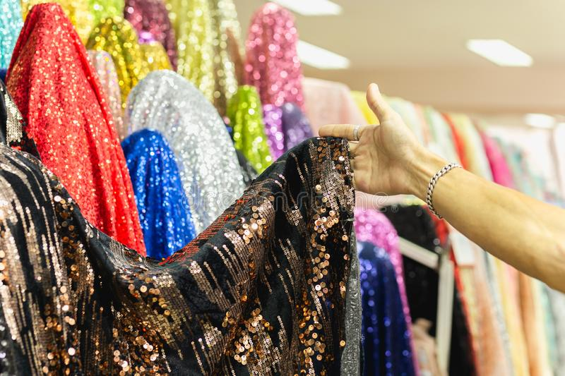 Hand pick a roll of Sequin fabric cloth in fabric store. royalty free stock images