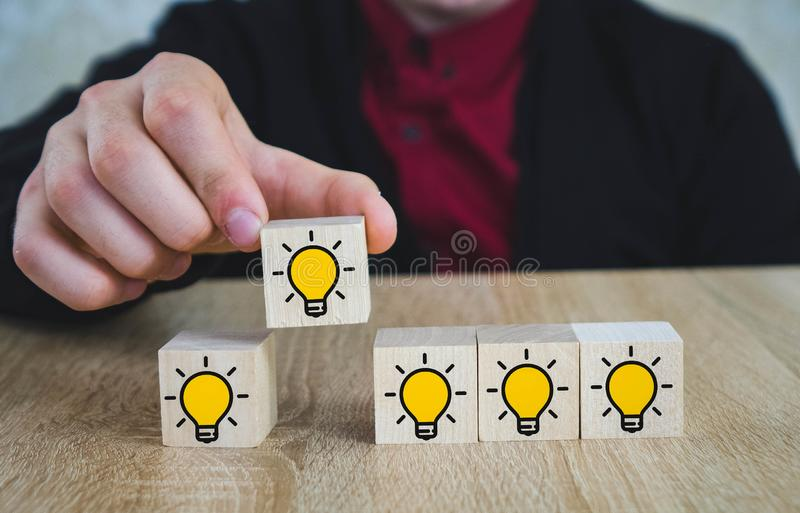 Hand picked a wooden cubes with the yellow light bulb symbol on wooden table. New idea, Innovation and Solution concepts stock photo