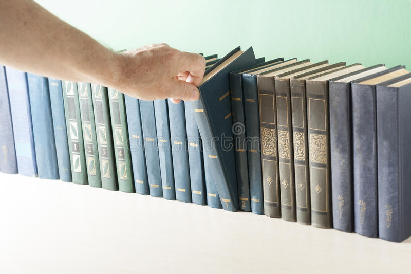 Hand picking book from the shelf in library.  stock photos