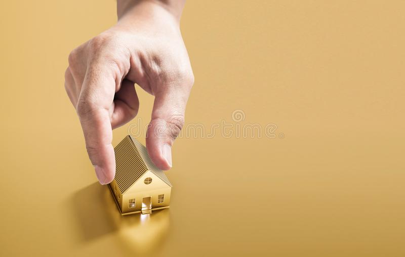 Hand picking golden house, real estate investment and buying home concept. S royalty free stock photography