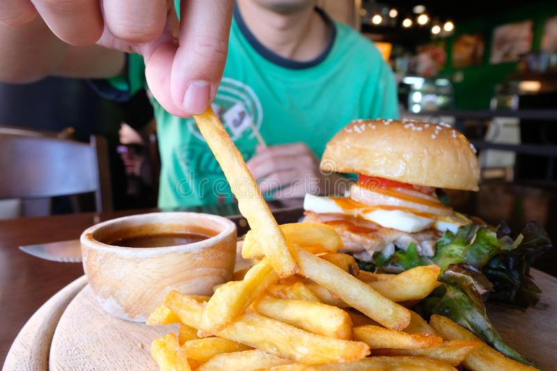 Hand picking a piece of french fries.A set of famous fast food. Golden fries and Hamburger on wooden plate. Restaurant's royalty free stock photo
