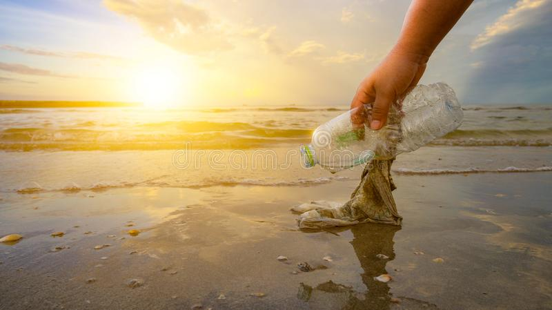 The hand is picking up trash on the beach, the idea of environmental conservation. The hand is picking up trash on the beach, the idea of environmental stock images