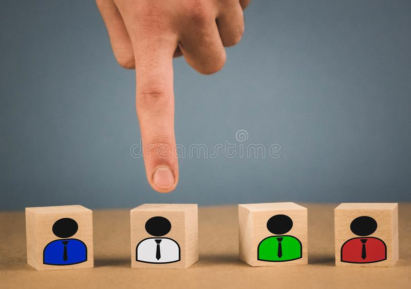 hand picks a wooden cube with a man in a white shirt stock photo