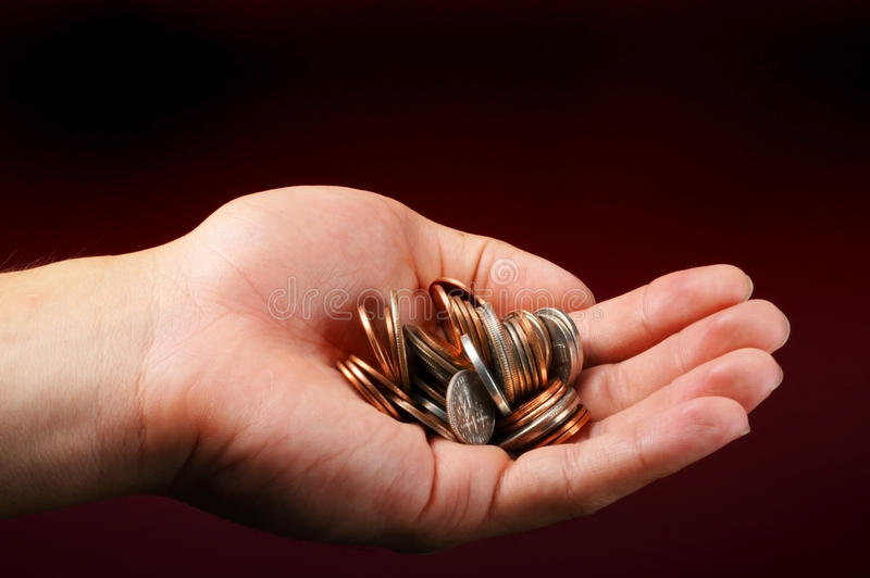 Hand with pile of change royalty free stock image