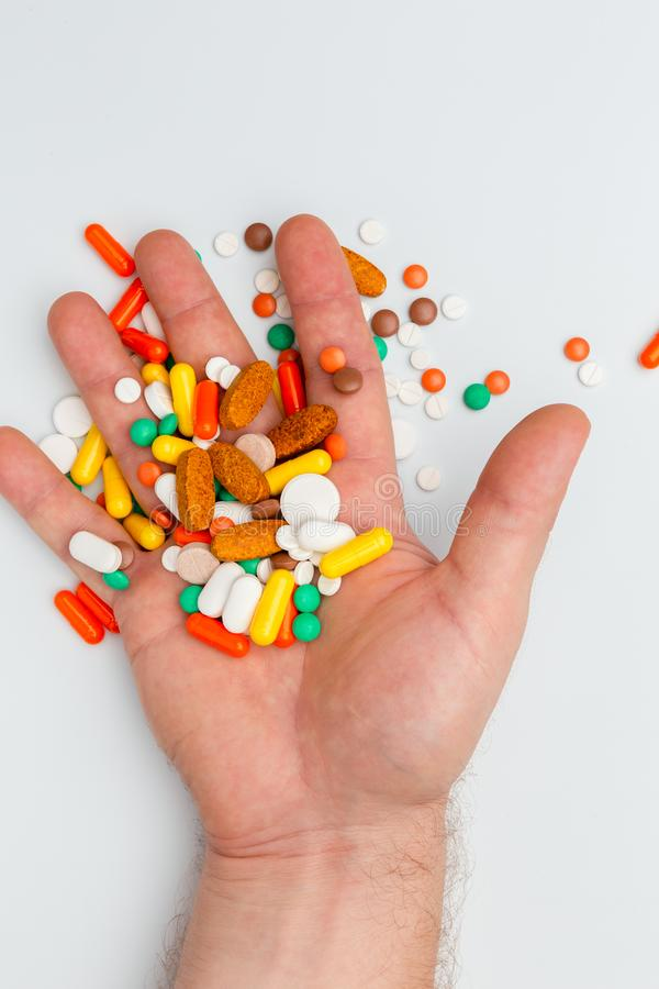 Hand with pills and capsules of different colors on white. Hand with pills and capsules of different colors and shapes, top view, close up, on white background stock photo