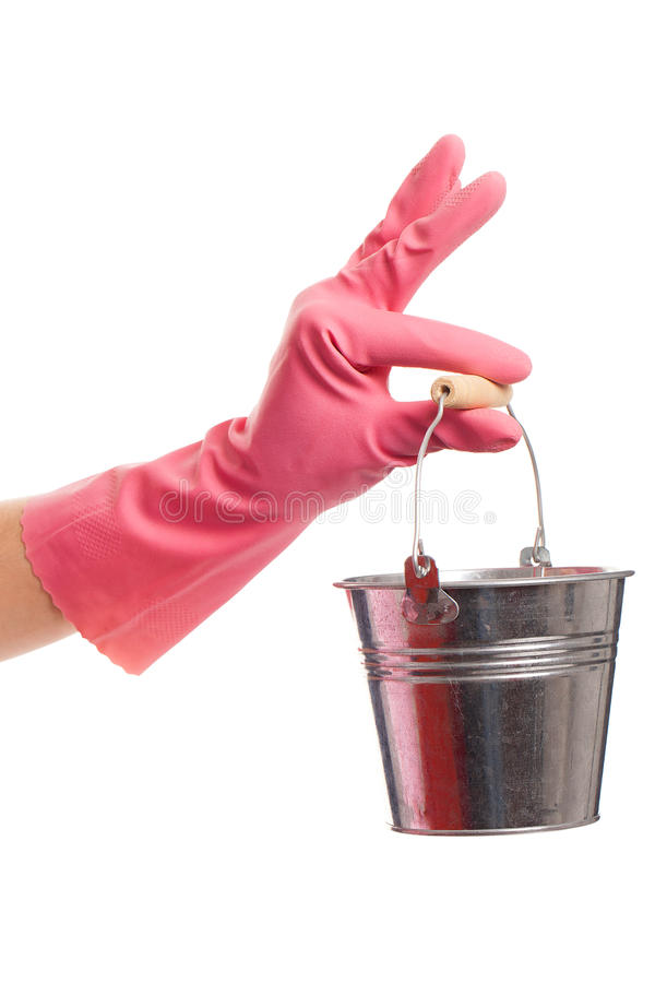 Hand in a pink glove holding silver pail. Hand in a pink domestic glove holding silver pail isolated over white background stock photography