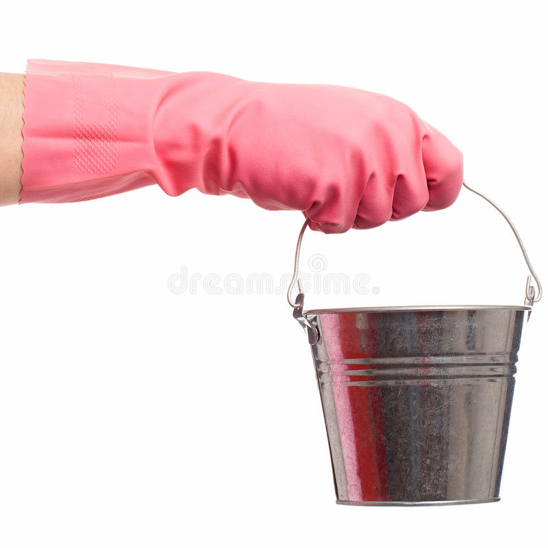 Hand in a pink glove holding silver pail. Hand in a pink domestic glove holding silver pail isolated over white background royalty free stock photos