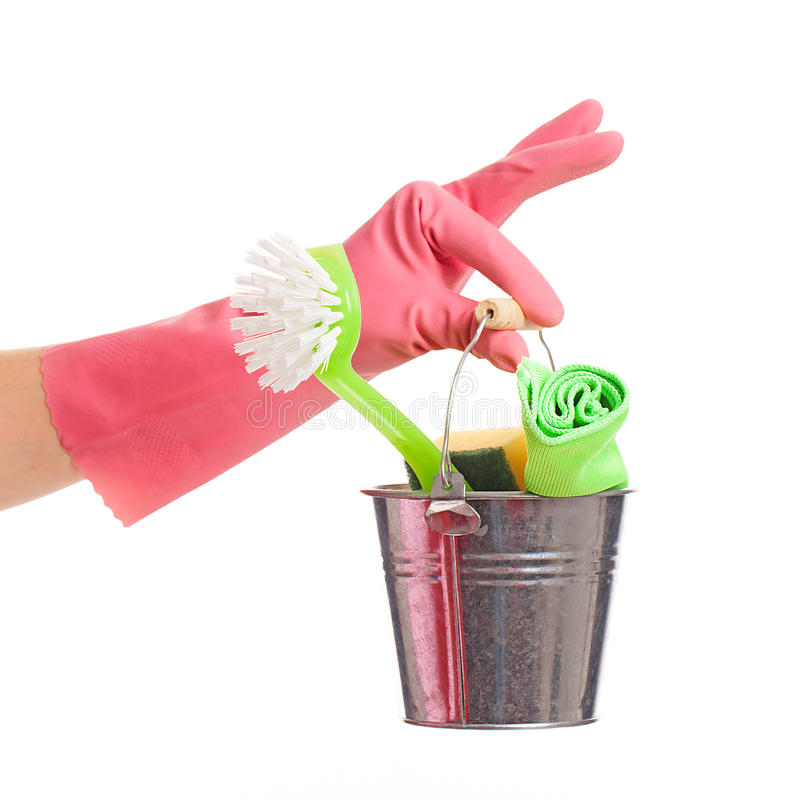 Hand in a pink glove holding silver pail. Hand in a pink domestic glove holding silver pail isolated over white background royalty free stock image