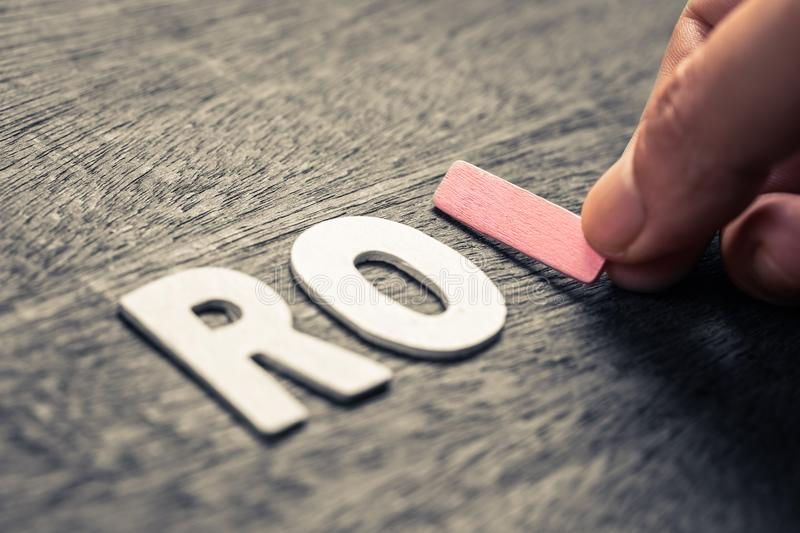 ROI WOOD LETTERS. Hand place wood letters for ROI Return On Investment concept stock photography