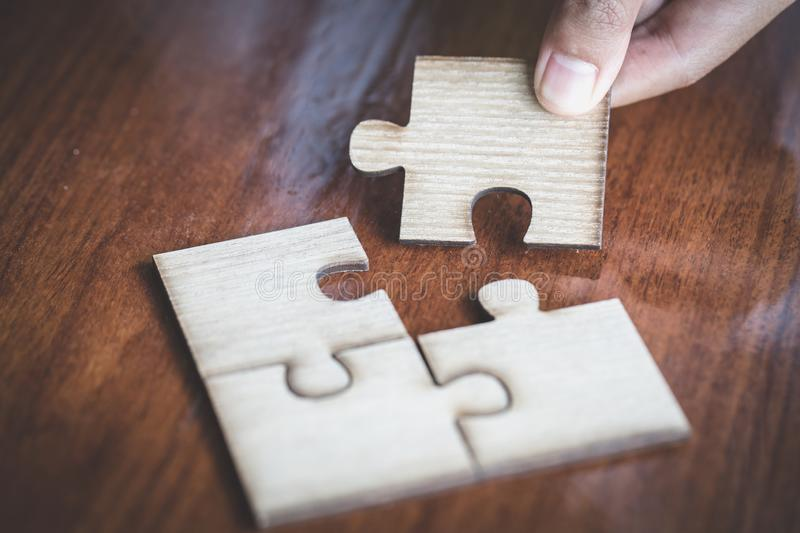 Hand placed the last piece of jigsaw puzzle, conceptual of problem solving, finding a solution stock images