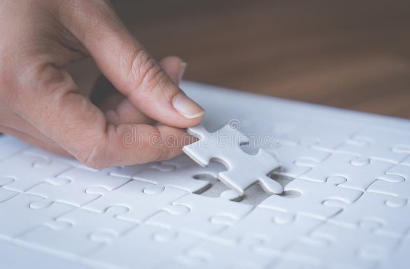 Hand placing the last jigsaw for business solution royalty free stock images