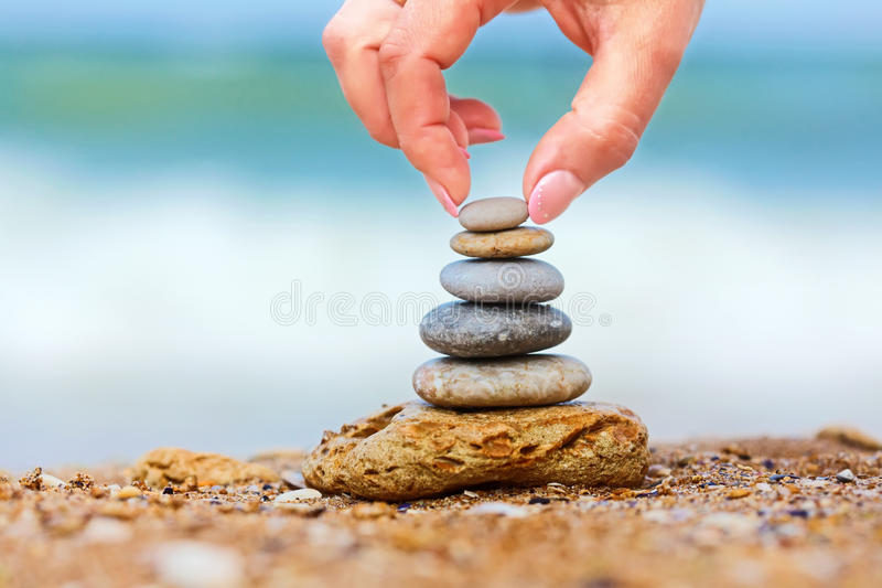 Hand placing the last pebble of a stacked tower