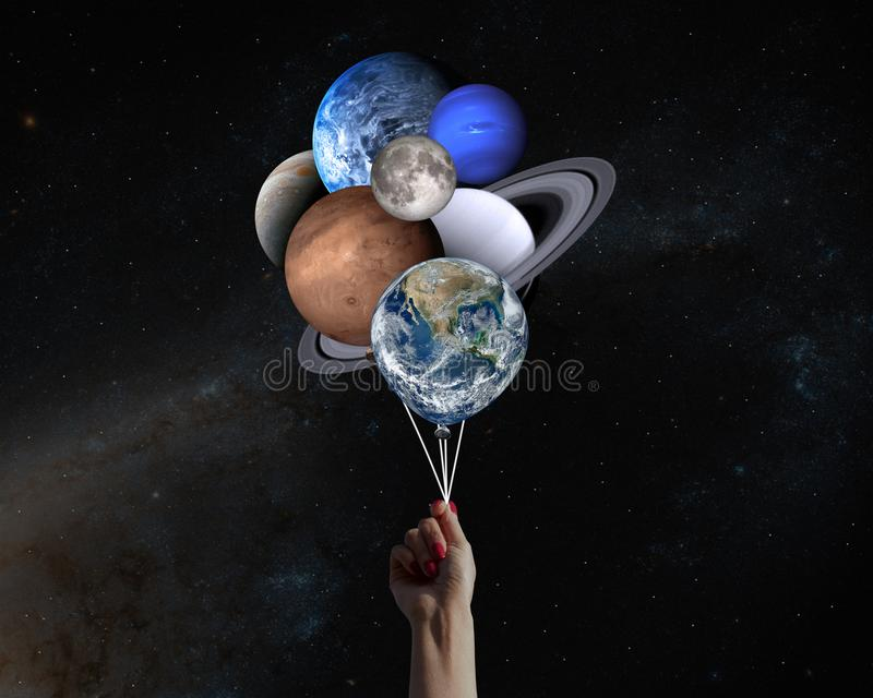 Hand with planets shaped balloons in solar system. Elements of this image furnished by NASA.  royalty free illustration