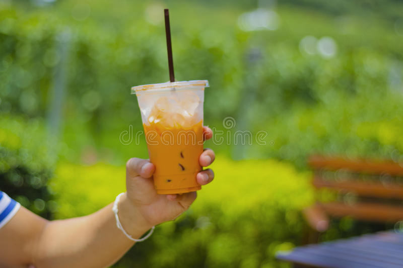 Hand with plastic glass of iced tea on table. royalty free stock photo