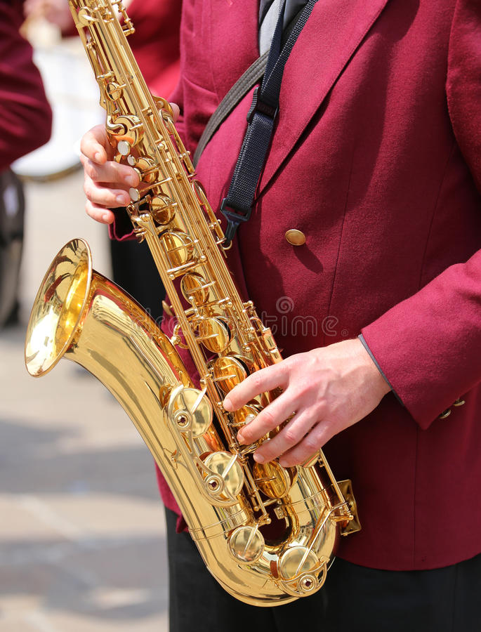 Hand of player and the golden saxophone. Hand of player and the saxophone during the live concert royalty free stock images