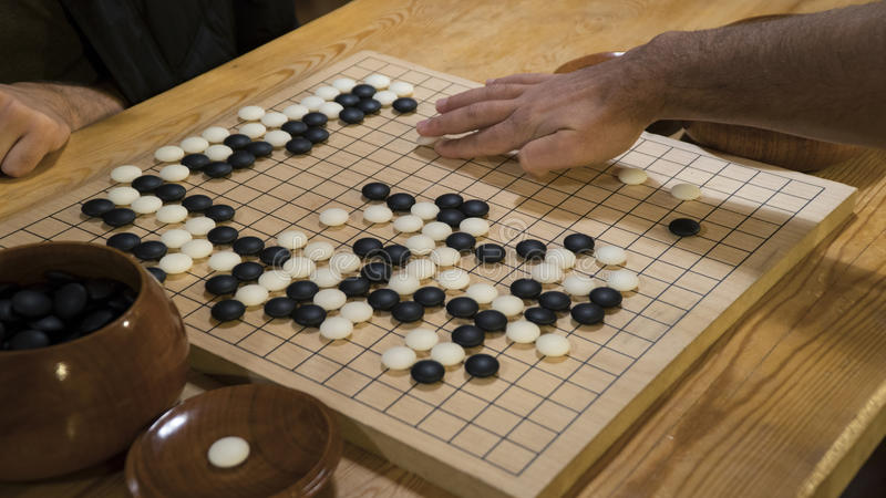 Hand playing black and white stone pieces on Chinese Go or Weiqi game board. Indoor activity with artificial light. Hand playing black and white stone pieces on royalty free stock photo