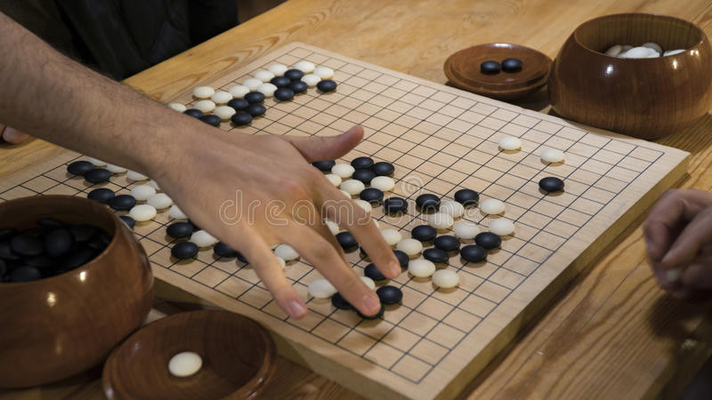 Hand playing black and white stone pieces on Chinese Go or Weiqi game board. Indoor activity with artificial light. Hand playing black and white stone pieces on royalty free stock photography