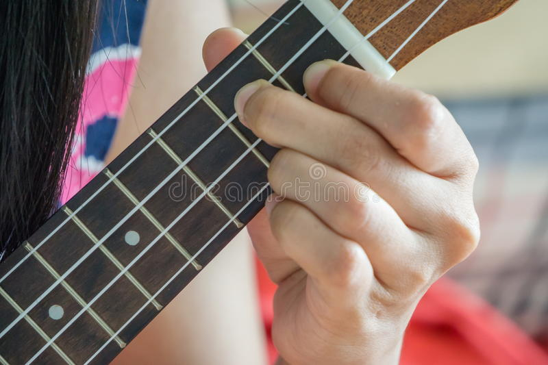 Hand playing guitar or Ukulele chord royalty free stock images