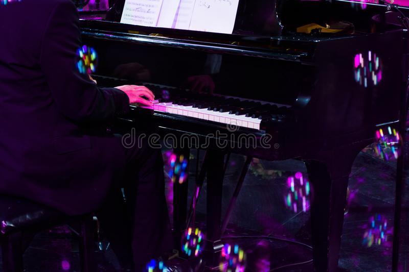 Hand playing on piano in harsh concert lighting royalty free stock photo