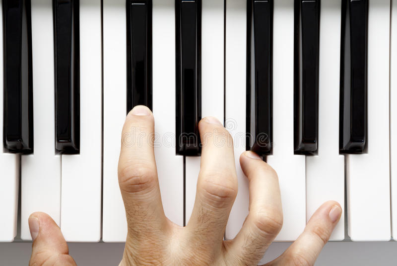 Hand playing piano. A hand playing the piano from a high angle view stock images